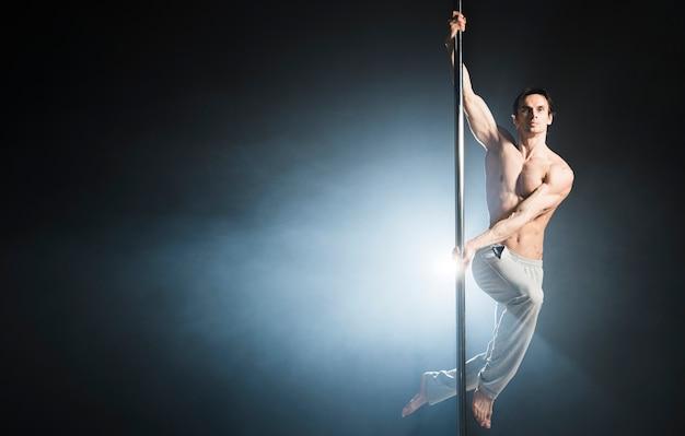 Retrato do modelo masculino atraente, realizando uma dança do poste Foto gratuita