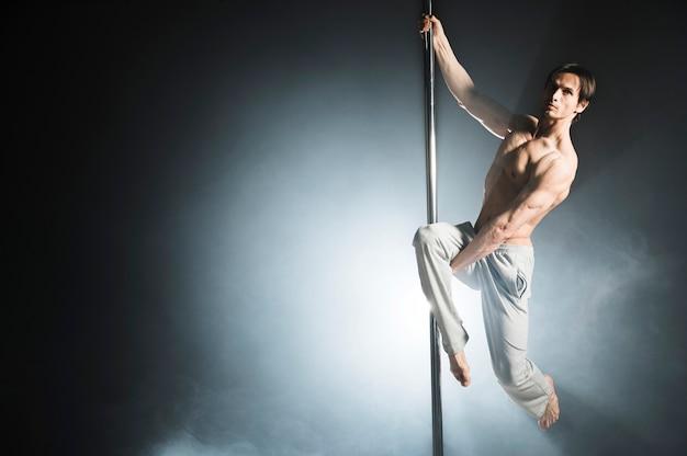 Retrato do modelo masculino forte, realizando uma dança do poste Foto gratuita