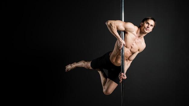 Retrato do modelo masculino, realizando uma dança do poste Foto gratuita