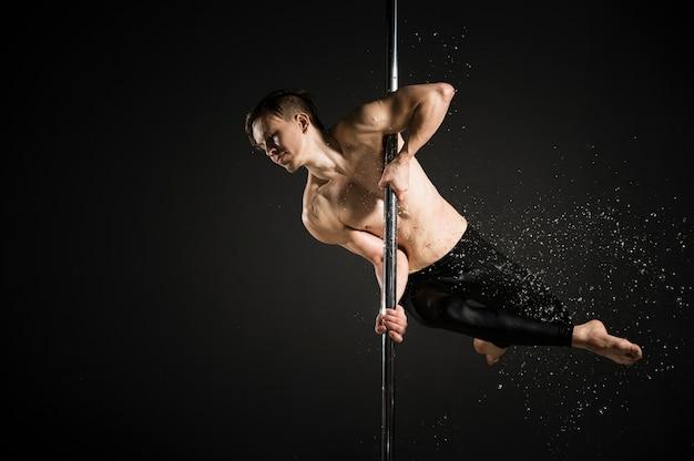 Retrato do modelo profissional masculino, realizando uma dança do poste Foto gratuita