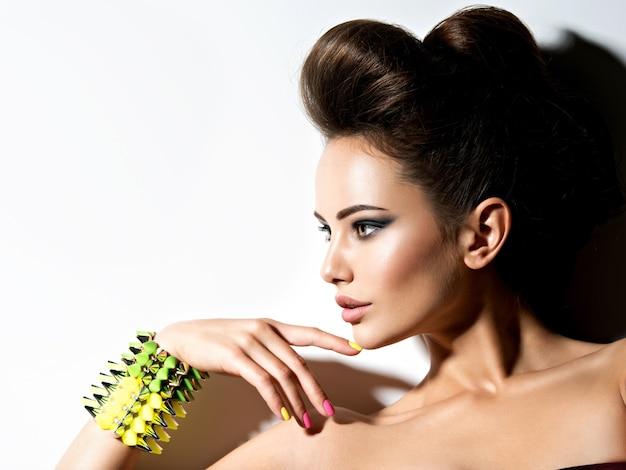 Retrato do perfil de uma linda mulher usando pulseira com espinhos e unhas multicoloridas Foto gratuita