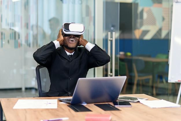 Retrato do profissional afro-americano novo que usa a realidade virtual aumentada no escritório moderno do sotão. tecnologia vr Foto Premium