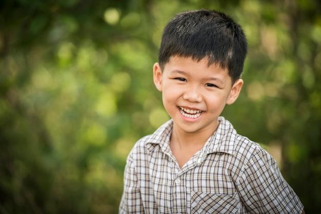 Retrato do rapaz pequeno feliz que ri quando jogar no parque. Foto gratuita