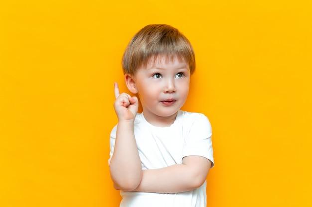 Retrato do rapaz pequeno louro considerável bonito com o dedo apontado acima. criancinha tem idéia. miúdo isolado no blackground amarelo. sucesso, ideia brilhante, ideias criativas Foto Premium