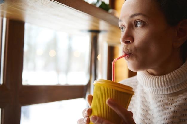 Retrato do rosto de uma jovem bebendo uma bebida saborosa de um canudo e olhando pela janela para uma natureza coberta de neve Foto Premium