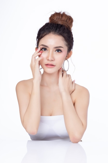 Retrato do sorriso asiático de assento da mulher atrativa no fundo branco. Foto Premium