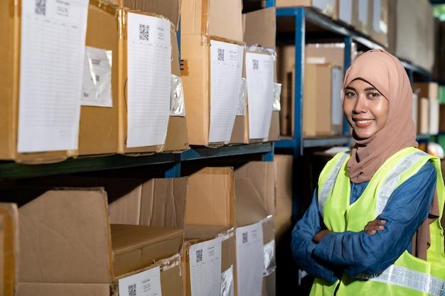 Retrato do trabalhador islâmico feminino armazém cruzou o braço na frente da prateleira do produto com cartão de estoque no ambiente de distribuição do armazém. para inventário de armazém comercial e conceito logístico. Foto Premium