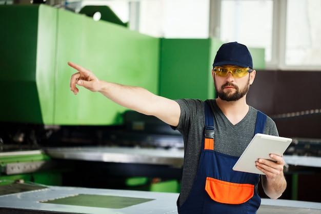 Retrato do trabalhador que aponta o dedo no lado, fundo da fábrica de aço. Foto gratuita