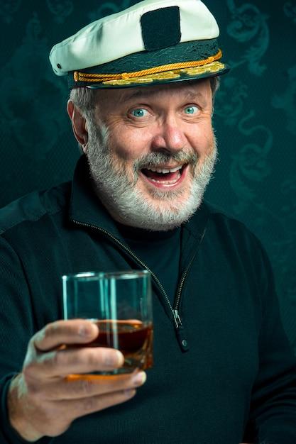 Retrato do velho marinheiro como capitão de camisola preta e chapéu bebendo conhaque no studio preto Foto gratuita