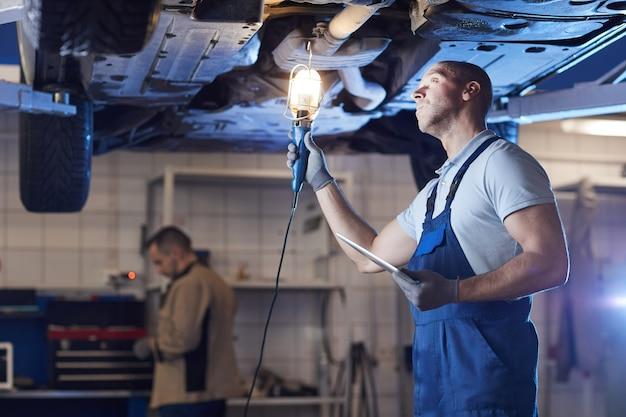 Retrato dramático de um mecânico musculoso sob o carro no elevador enquanto inspeciona o veículo na oficina mecânica, copie o espaço Foto Premium