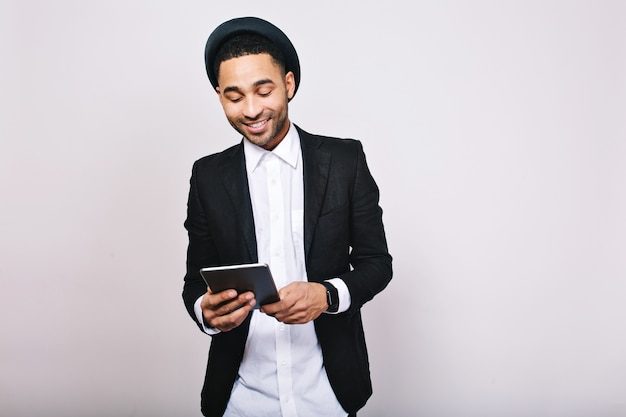 Retrato elegante elegante homem bonito na camisa branca e jaqueta preta com tablet. empresário, grande sucesso, trabalho, bom humor, sorrindo Foto gratuita