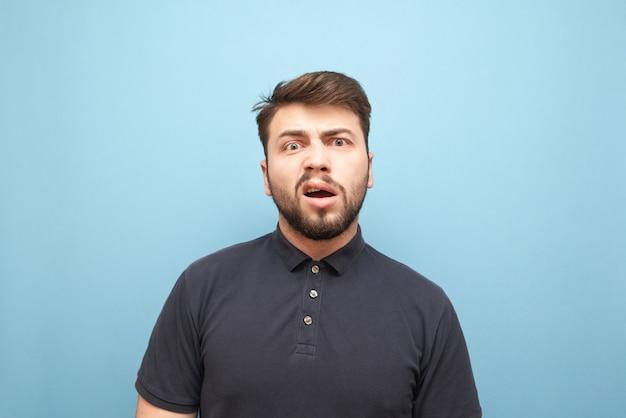 Retrato em close-up de um homem emotivo com barba, rosto surpreso e zangado Foto Premium