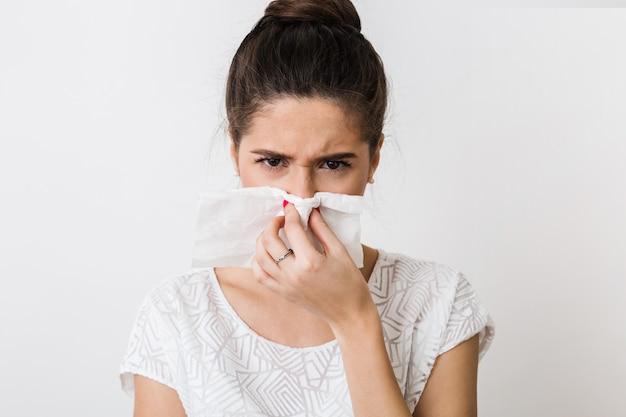 Retrato em close-up de uma mulher bonita assoando o nariz com um guardanapo, resfriada, sentindo-se doente, isolada,, carrancuda Foto gratuita