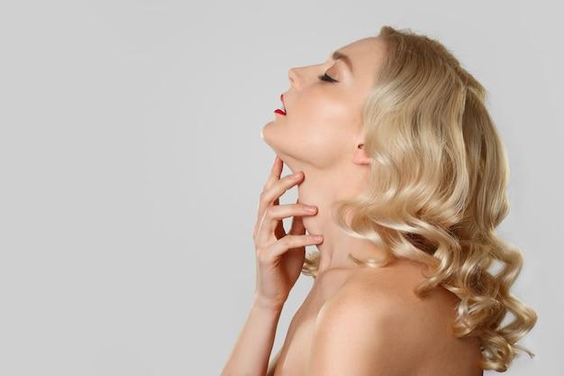 Retrato, em, perfil, de, loiro, menina, com, cabelo ondulado, tocar, dela, garganta Foto Premium