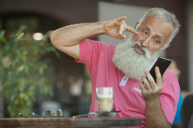 Retrato emocional de um homem de negócios maduros alegre e elegante, com uma cabeça careca, com um sorriso falando no smartphone com um amigo. homem barbudo sênior Foto Premium