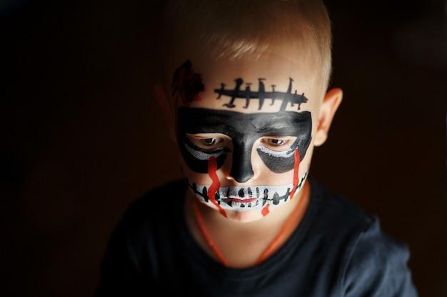 Retrato emocional de um menino com um zumbi assustador no rosto Foto Premium
