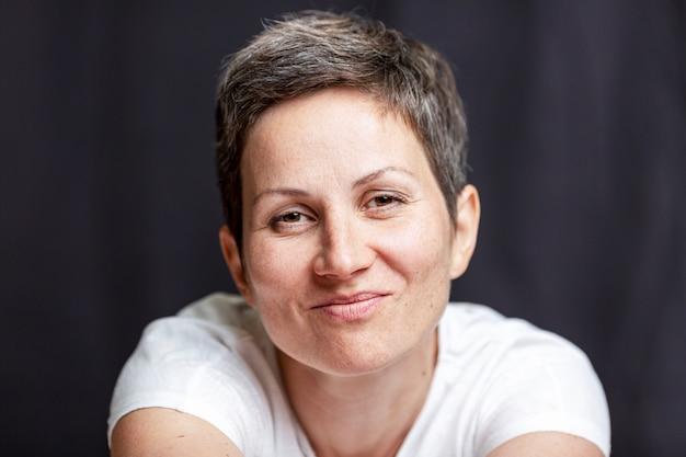 Retrato emocional de uma mulher adulta com cabelo curto. fundo preto. Foto Premium