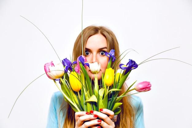 Retrato engraçado de estúdio de mulher loira fechar seu rosto por lindo buquê de tulipas coloridas, tons pastel suaves, vestido vintage, cabelos longos, detalhes de moda. a primavera está chegando Foto gratuita