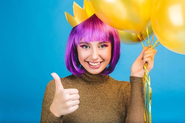Retrato feliz comemorando momentos de jovem alegre com balões dourados sorrindo. vestido de luxo, corte de cabelo roxo, coroa de princesa, bom humor. Foto gratuita