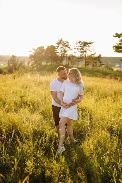 Retrato feliz de amar o casal em um passeio no parque em um dia ensolarado. Foto gratuita