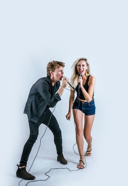 Retrato feliz do casal segurando o microfone e cantar uma canção Foto gratuita