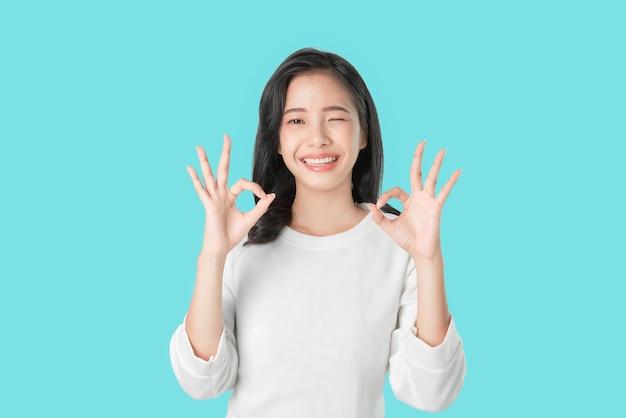 Retrato feliz mulher asiática mostra sinal de ok e sorrindo Foto Premium
