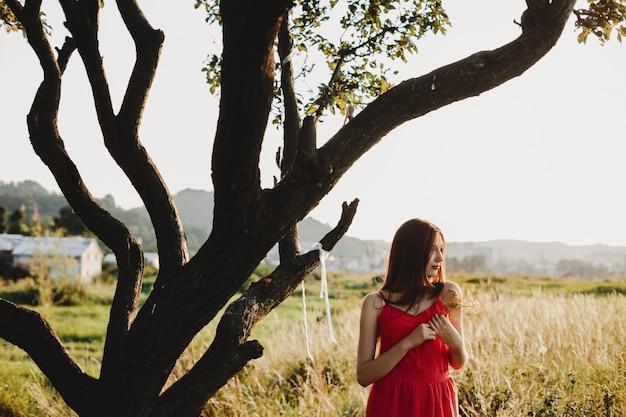Retrato feminino. encantadora mulher de vestido vermelho fica sob o ol Foto gratuita