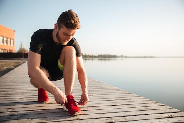 Retrato, homem, amarrar, cadarços, sapato esportes Foto gratuita