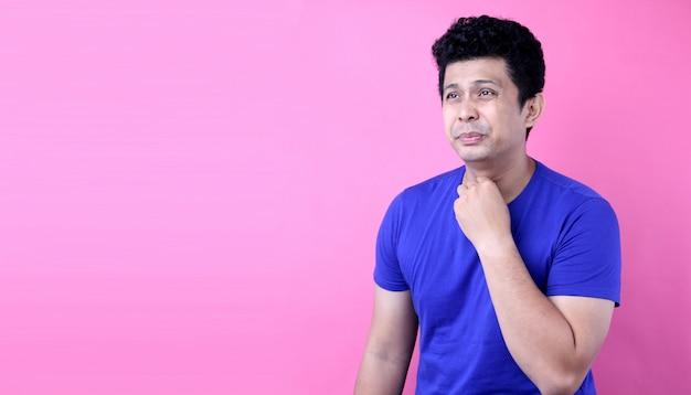 Retrato homem bonito da ásia há uma dor de garganta no fundo rosa no estúdio Foto Premium