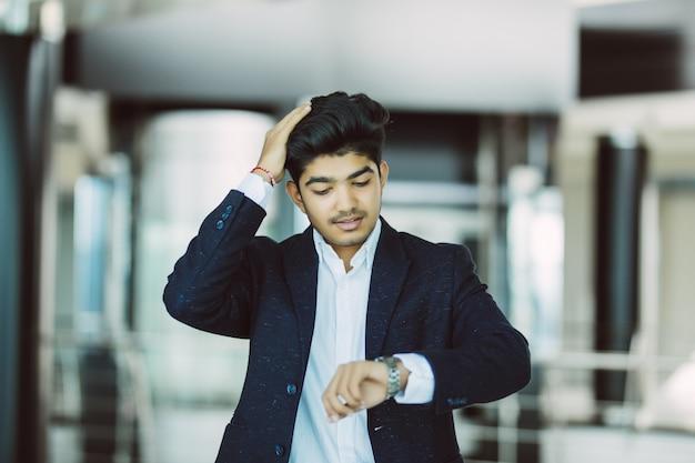 Retrato, homem negócios, observar, relógio, escritório Foto gratuita