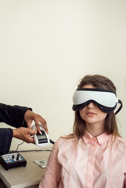 Retrato horizontal de bonito paciente do sexo feminino europeu sentado no consultório oftalmológico, usando rastreador de visão digital enquanto testava a visão, esperando o optometrista terminar o check-up Foto gratuita