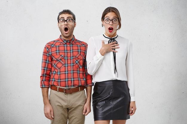 Retrato horizontal de homens e mulheres espertos em choque com a boca aberta Foto gratuita