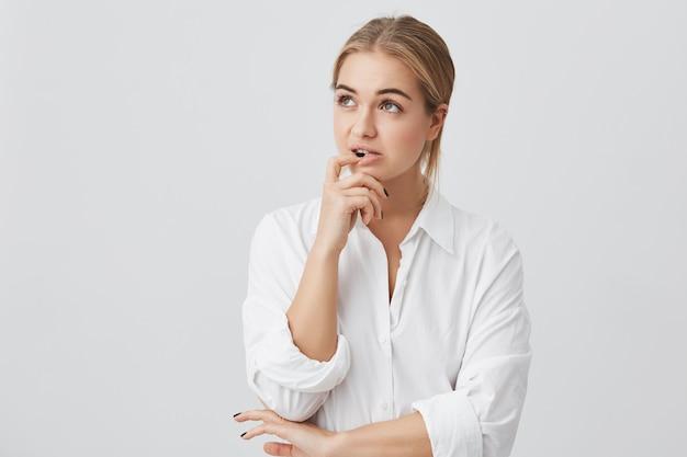 Retrato horizontal de mulher confusa com cabelos lisos tingidos, segurando o dedo nos dentes, fazendo uma escolha difícil, sem saber o que escolher. Foto gratuita