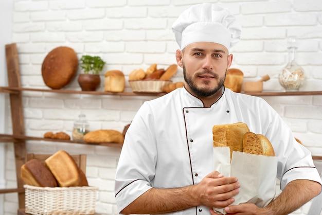 Retrato horizontal de um padeiro jovem bonito sorrindo alegremente posando em sua padaria com pão recém-cozido em um saco de papel copyspace consumismo compras compras comida serviço amigável trabalho. Foto gratuita