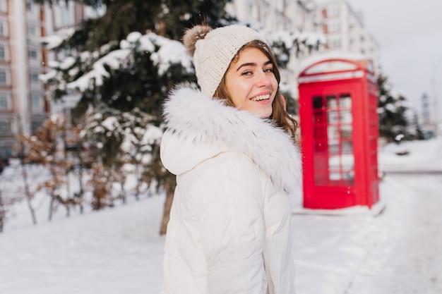 Retrato incrível sorridente jovem inverno andando na rua cheia de neve na manhã ensolarada. cabine telefônica vermelha, estilo britânico, aproveitando o frio Foto gratuita