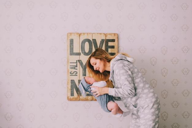 Retrato interior da jovem hapy em pijama segurando, abraçando o bebê recém-nascido perto da parede com placa decorativa. mãe cuida de seu filho infantil. conceito de maternidade. amor é tudo que você precisa Foto Premium