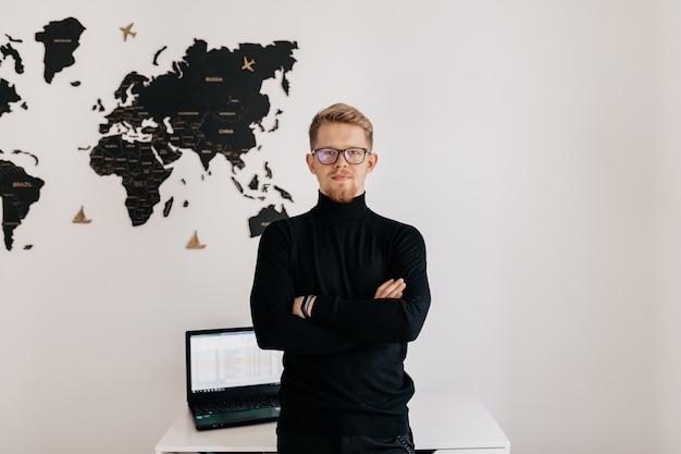 Retrato interior de homem loiro bonito vestindo roupas espetaculares e pulôver preto posando sobre uma parede branca com o mapa-múndi e o laptop no desktop. Foto gratuita