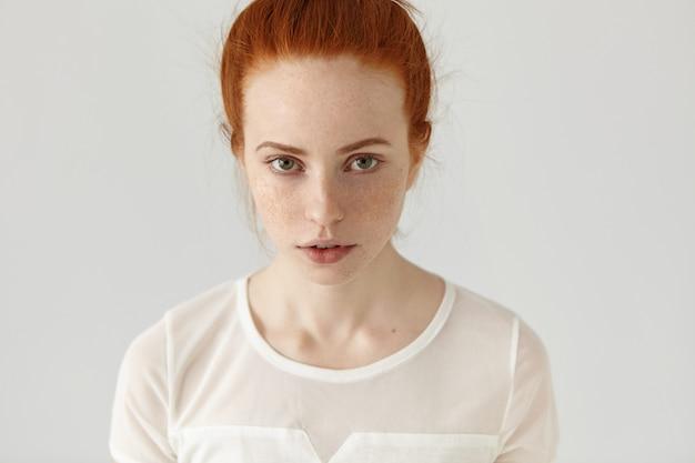 Retrato interior do modelo feminino ruiva jovem bonito sério com sardas e olhos verdes. menina bonita com cabelo ruivo coque vestindo blusa branca, tendo o resto dentro de casa Foto gratuita