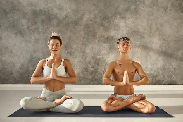 Retrato interno de dois jovens descalços, homem e mulher com corpos fortes e flexíveis, meditando em uma esteira durante a aula de ioga, sentados na postura de lótus, fechando os olhos e segurando as mãos em namaste Foto gratuita
