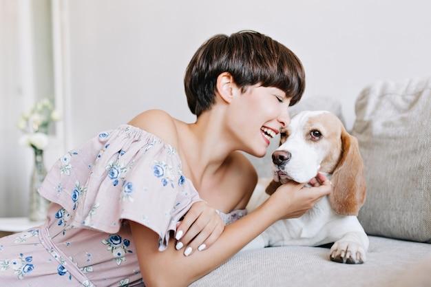 Retrato interno de uma jovem animada com um cabelo castanho-escuro brilhante arranhando o cachorro beagle com um sorriso Foto gratuita