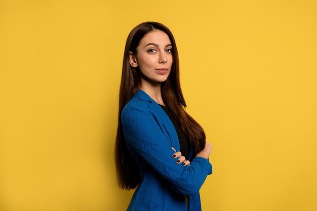 Retrato interno de uma jovem bem-sucedida com longos cabelos escuros e jaqueta azul, posando com os braços cruzados sobre uma parede amarela Foto gratuita