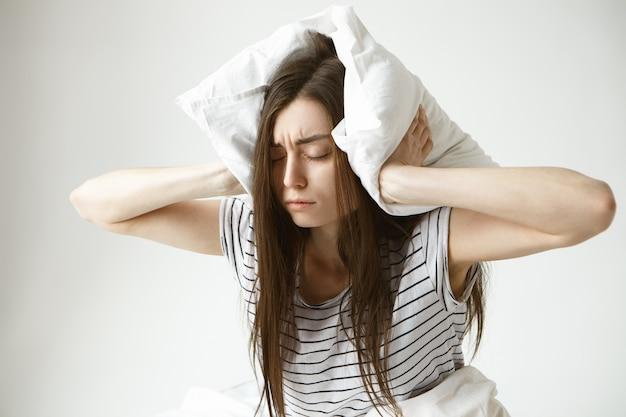 Retrato isolado de uma jovem morena estressada usando um pijama listrado cobrindo as orelhas com um travesseiro branco e sentindo-se frustrada porque ela não consegue dormir à noite por causa do marido roncando Foto gratuita