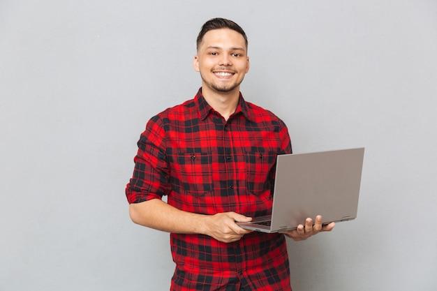 Retrato, jovem, homem, camisa xadrez, segurando, laptop Foto gratuita