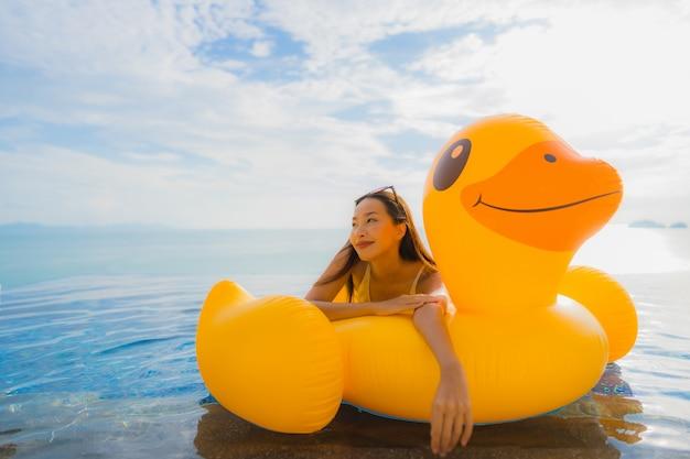Retrato, jovem, mulher asian, ligado, inflável, flutuador, pato amarelo, ao redor, piscina ao ar livre, em, hotel, e, recurso Foto gratuita