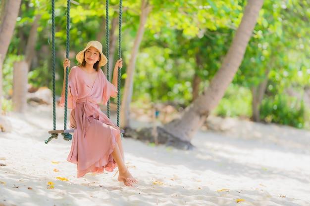 Retrato, jovem, mulher asian, sentando, ligado, balanço, corda, e, mar, ao redor, praia, mar, oceânicos, coqueiro, palma Foto gratuita