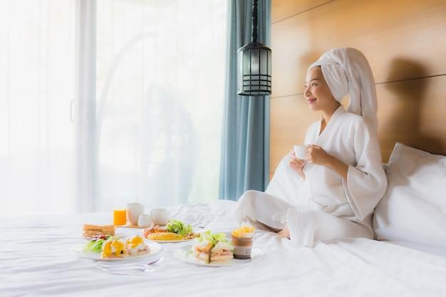 Retrato jovem mulher asiática na cama com café da manhã no quarto Foto gratuita