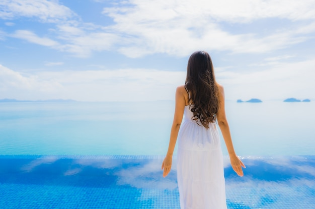 Retrato jovem mulher asiática relaxar sorriso feliz ao redor da piscina no hotel e resort Foto gratuita