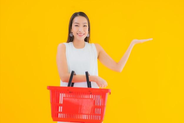 Retrato linda jovem asiática com cesta de compras para fazer compras no supermercado Foto gratuita