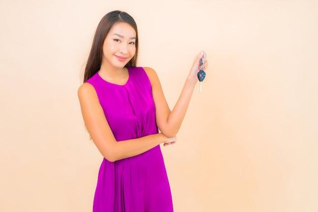 Retrato linda jovem asiática com chave do carro na cor de fundo isolado. Foto gratuita