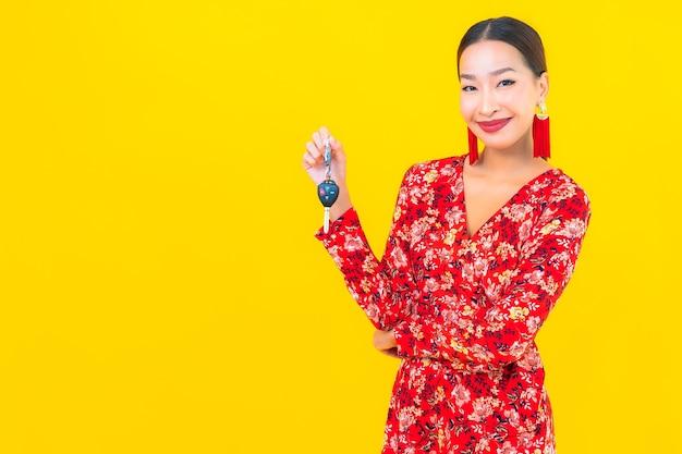 Retrato linda jovem asiática com chave do carro na parede amarela Foto gratuita